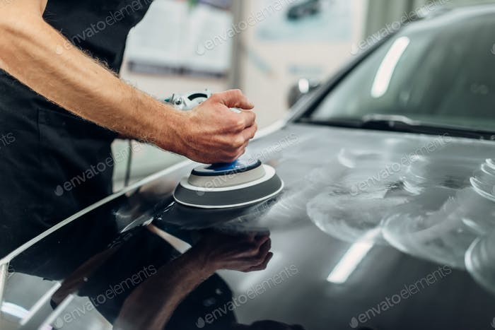 Male person with polishing machine cleans car hood