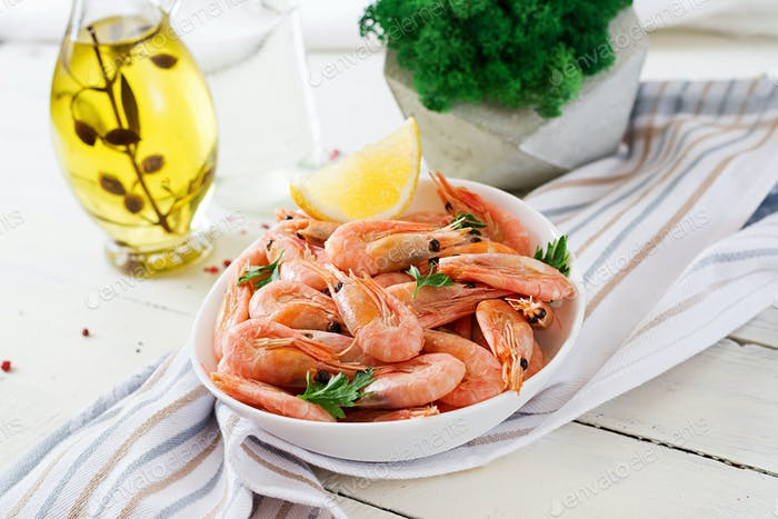 Boiled  shrimps or prawns on a white bowl on a white table. Seafood.