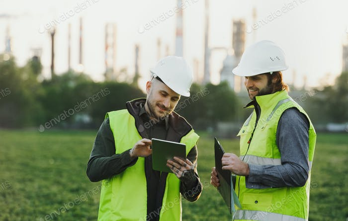 Two young engineers with tablet standing outdoors by oil refinery, discussing issues