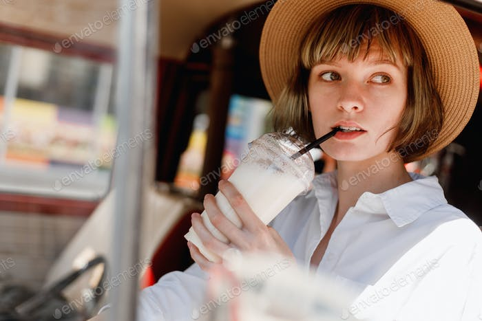 Young woman in a straw hat dressed in white shirt is driving a red minivan and drinking a milkshake