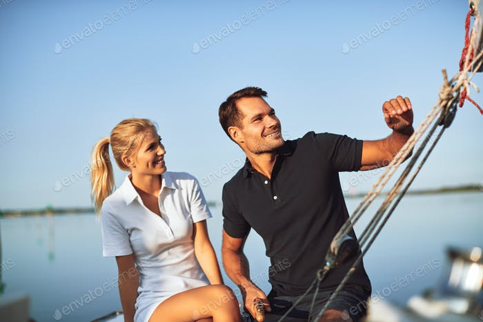 Smiling young couple sailing their yacht on a sunny day