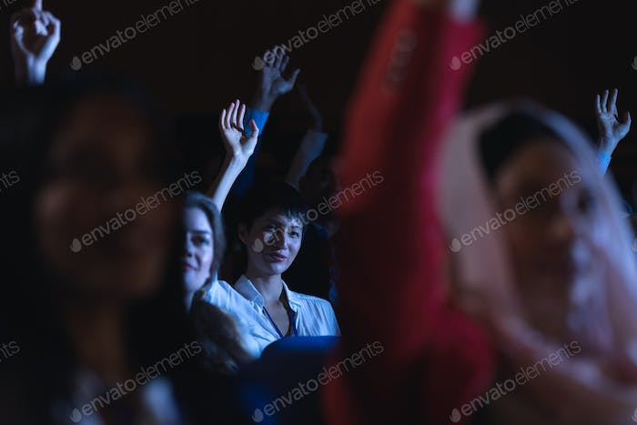 Low angle view of beautiful Asian businesswoman sitting and raising hand while sitting in auditorium