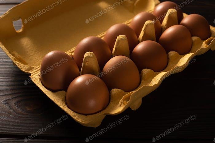 Huevos de pollo marrones en bandeja para huevos sobre fondo de madera marrón