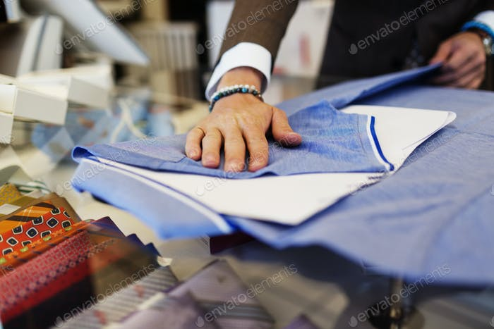 Sales clerk folding t-shirt on table in clothing showroom