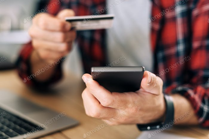 Online shopping from home office using smartphone and credit card
