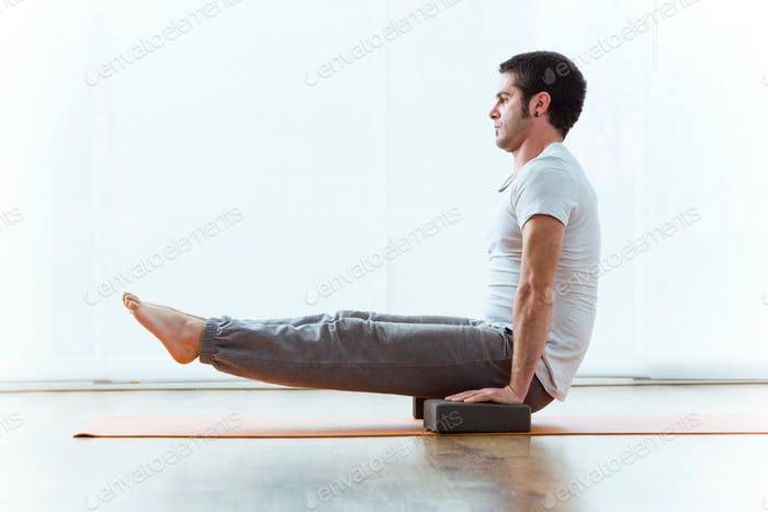 Handsome young man practicing yoga at home.