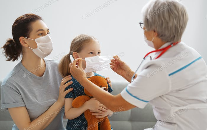Doctor, child and mother wearing facemasks