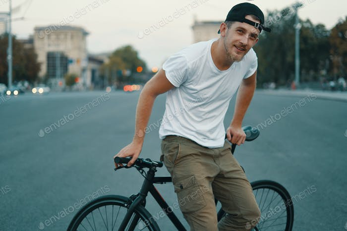 A Young, handsome man posing while sitting on bike, on city road