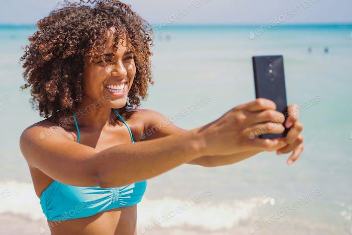 Cheerful ethnic woman taking selfie on beach