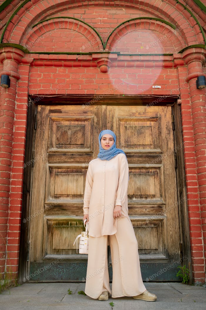 Young muslim woman in blue hijab and beige casualwear