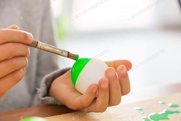 Boy in his room paints easter eggs with a brush