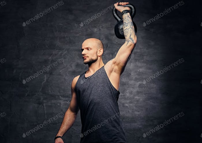 Sporty shaved head tattooed male doing shoulder workout with the Kettlebell.