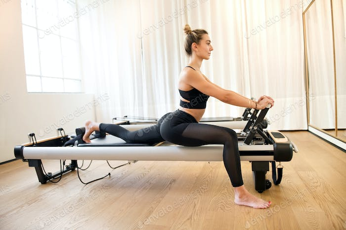 Woman stretching legs while on exercise machine