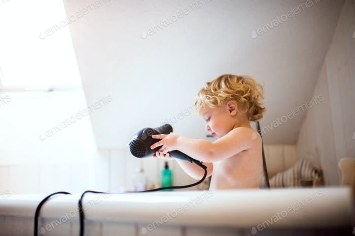 Toddler boy with hairdryer in the tub in the bathroom.
