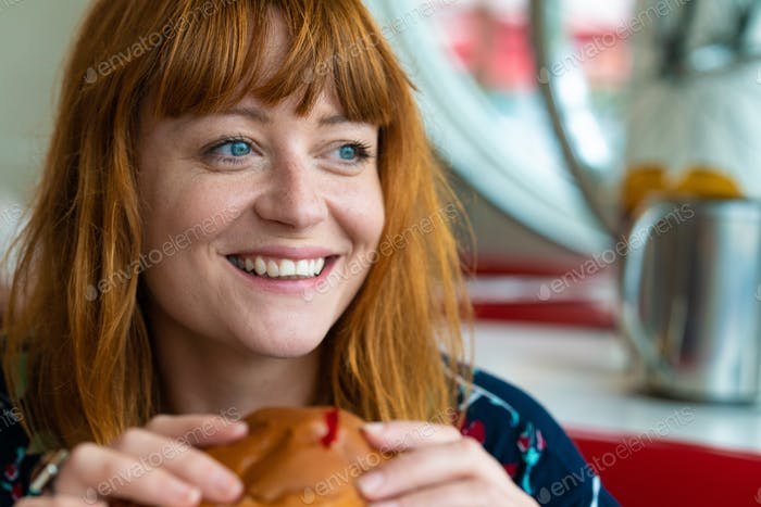 Portrait of ginger girl with blue eyes on a floral dress in diner