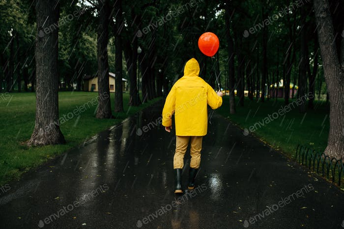 Sad man with balloon walking in park in rainy day