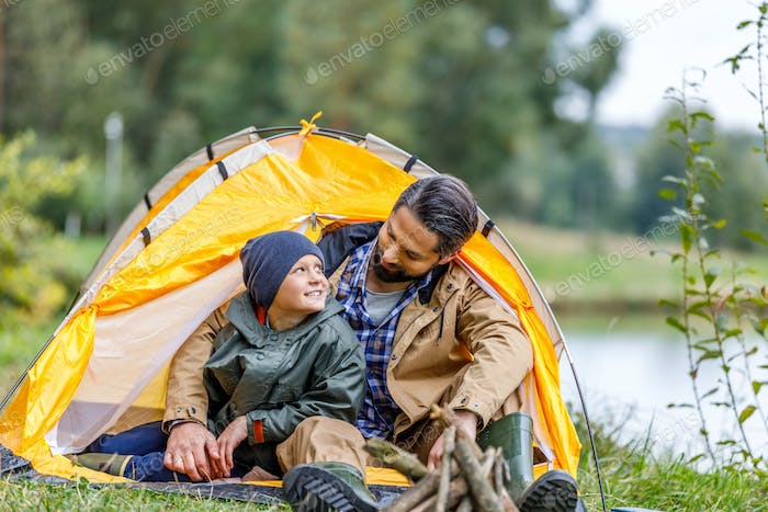 happy father and son sitting in tent in camping at countryside