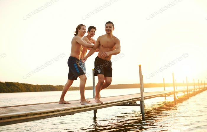 Zwei Freunde schieben einen Teenager in einen See