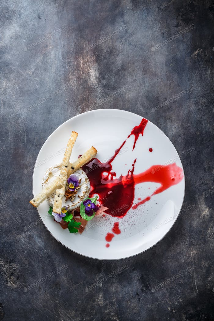 Grilled brie cheese with jam and walnuts on white plate, restaurant meal, copy space.
