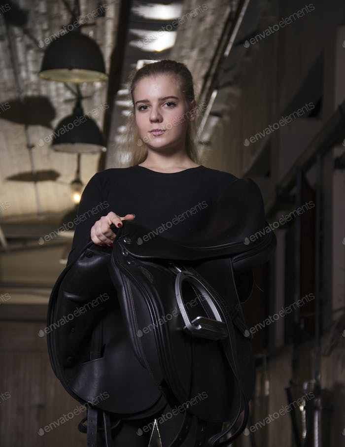 Young woman holding saddle at stable.