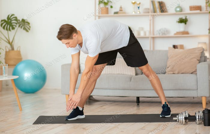Warm up and stretch in workout. Muscular guy doing stretching