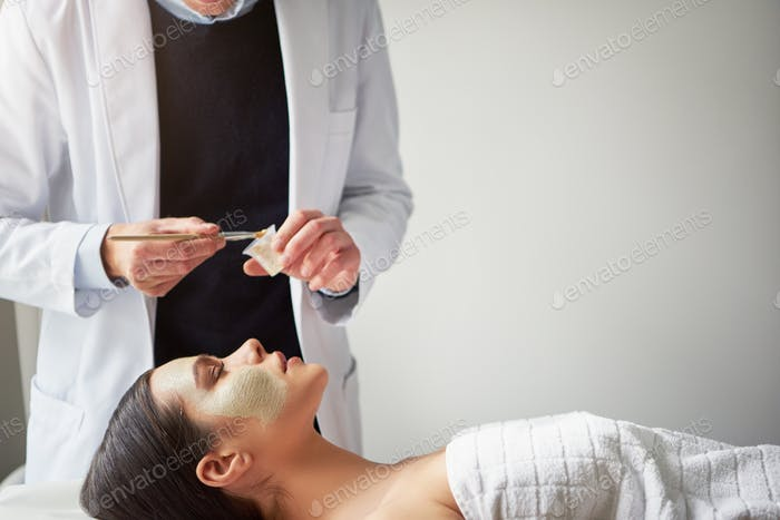 Unrecognizable beautician putting facial mask on woman