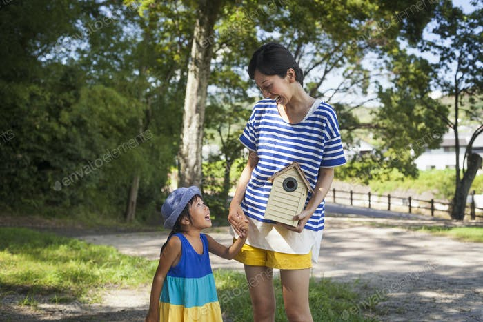 Mother and daughter standing outdoors, holding bird house.