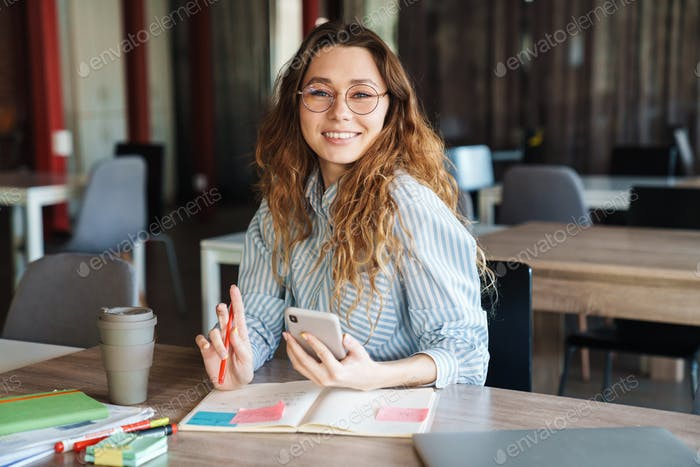 Image of joyful charming woman using cellphone while studying