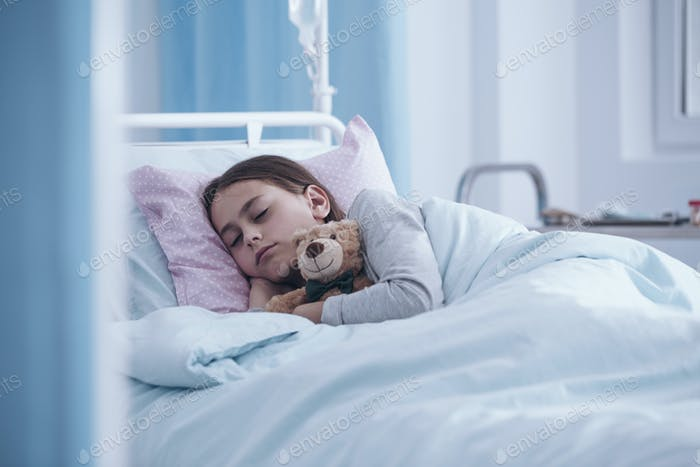 Sick girl sleeping with teddy bear in the hospital