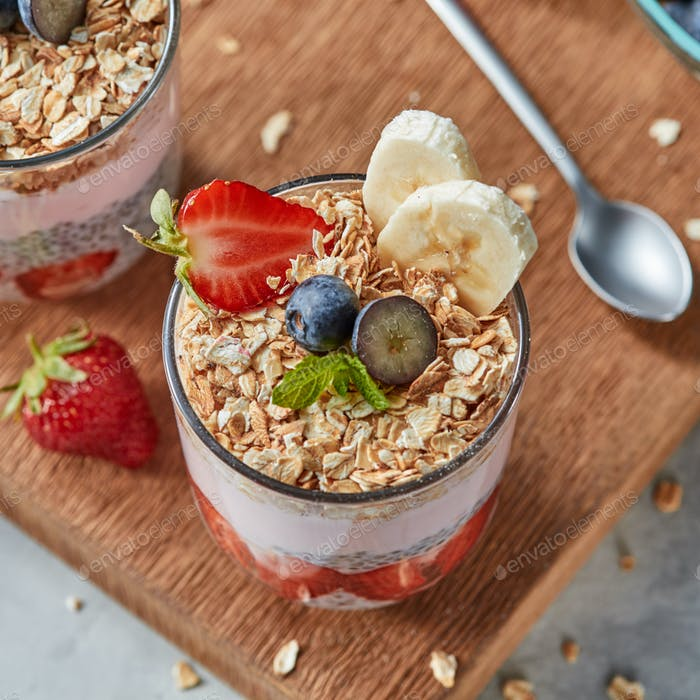 The glass with oat flakes, banana fruits, strawberries, fresh smoothie, chia seeds on a wooden board
