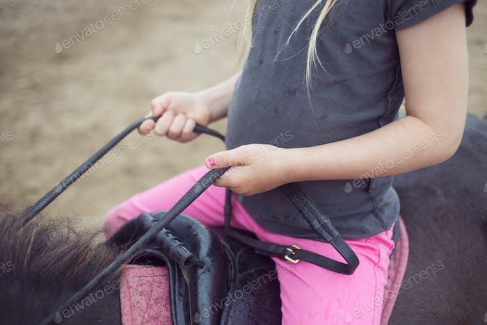 Close-up of girl (4-5) sitting on pony