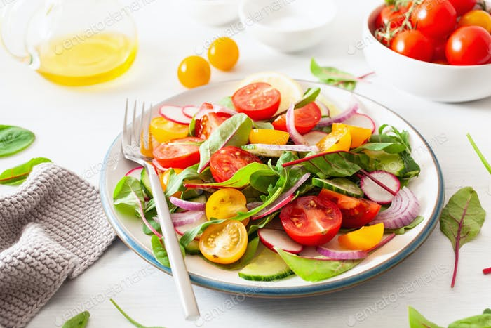 healthy colorful vegan tomato salad with cucumber, radish, onion