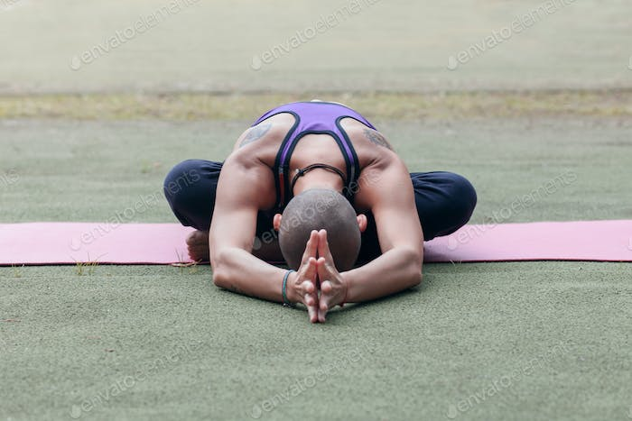 athletic woman doing yoga outdoor on summer lawn