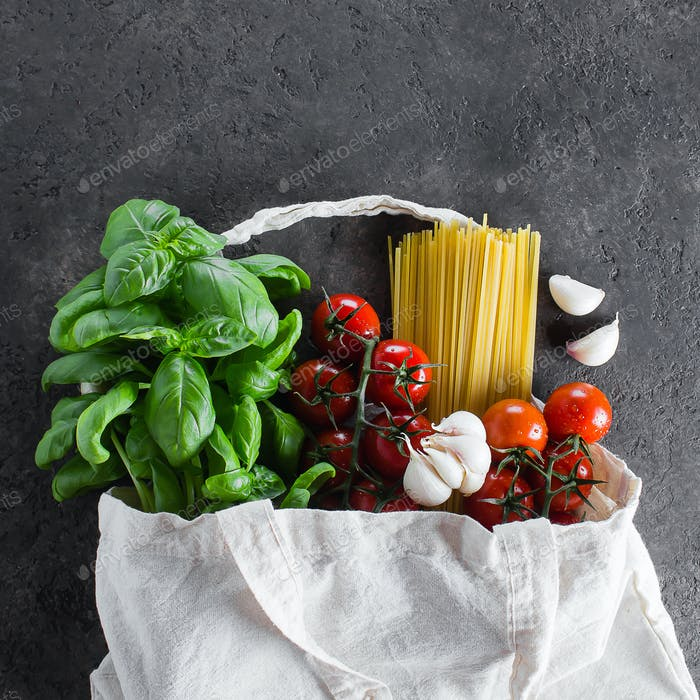 Healthy product for italian pasta in fabric bag on dark table. Reusable bag with groceries.