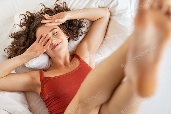 Woman waking up after sleep in her bed