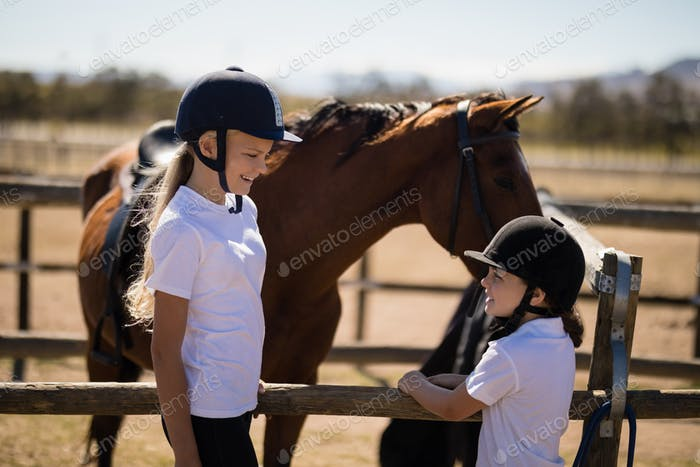 Smiling girls looking face to face near the brown horse in the ranch