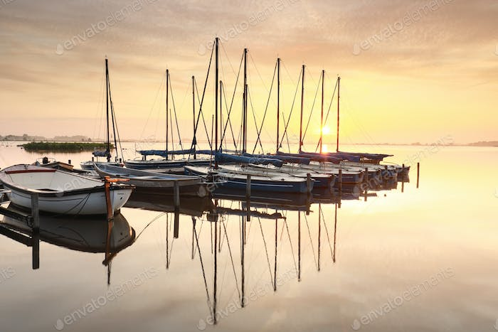 beautiful serene sunrise over lake with yachts