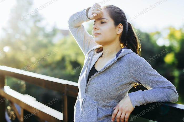 Beautiful woman resting after jogging outdoors