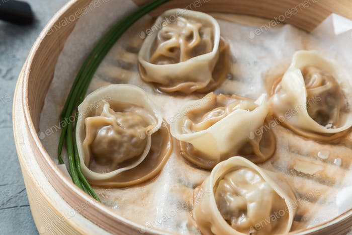 High angled view of cooked dumplings inside bamboo steamer with lip partially off.