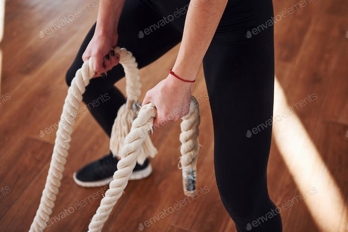 sportive young woman in black sportive clothes that standing with knots in hands in gym