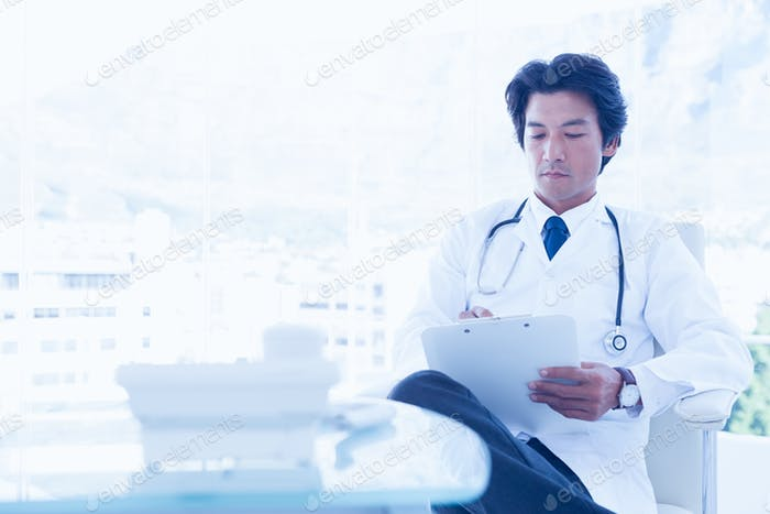 Focused doctor reading over notes in his office