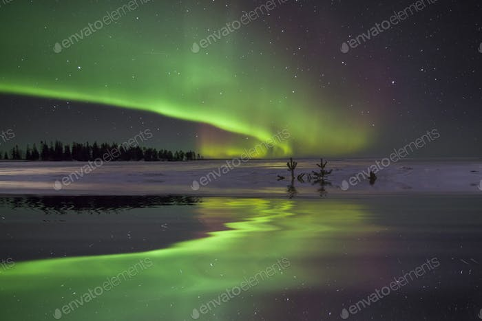 Amazing winter landscape with northern lights and stars.