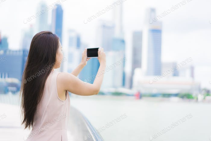Asian woman using smartphone or mobile phone for taking a photos