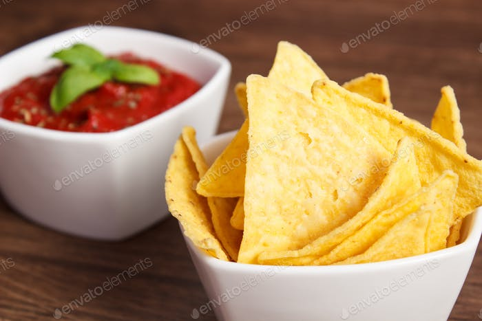 Salted potato crisps and sauce in white bowls on board, concept of unhealthy food