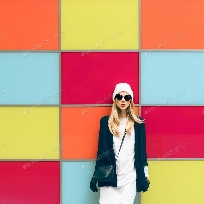 Fashionable blonde standing against a bright wall. urban style