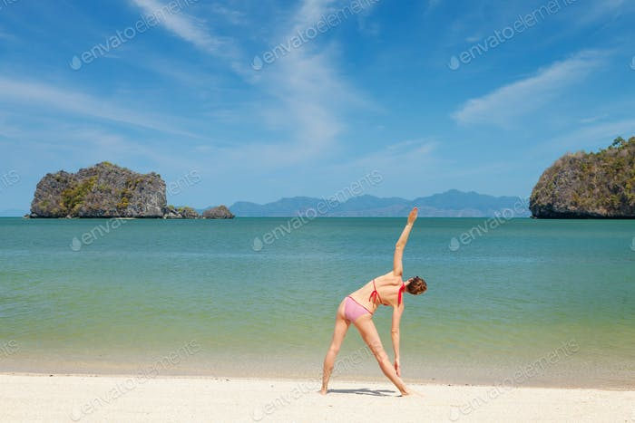 Young woman practice yoga on a sea beach