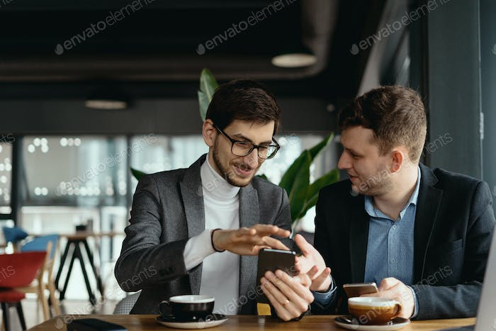 Two businessmen having a conversation using a smartphone