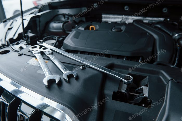 Group of objects. Repair tools lying down on the engine of automobile under the hood