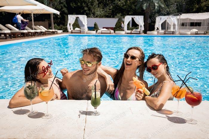 Empresa de chicas jóvenes alegres y chico que se relajan en la piscina, bebiendo cócteles y jugando
