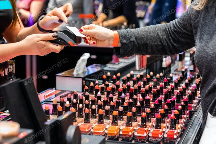 Customer woman paying for a products using credit card in beauty store